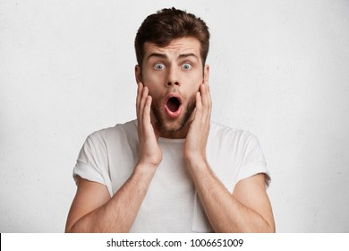 Isolated shot of surprised blue eyed male has beard, dressed in casual white t shirt, looks with bugged eyes, being shocked to be invited on business meeting with partners, doesn`t know what to wear