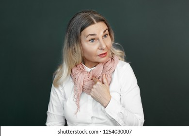 Isolated shot of surprised senior woman wearing white blouse and scarf pointing finger at her chest, feeling indignation while having unpleasant conversation or arguement, persisting in her opinion