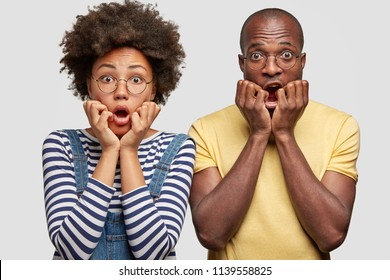 Isolated shot of terrific African American family couple keep hands under chins, stare with scared expressions, frightened by awful accident, isolated over white background. People and shock concept