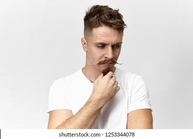 Isolated shot of thoughtful serious hipster guy with funny mustache looking down with pensive facial expression, touching his goatee beard, having some problem, searching for way to solve it