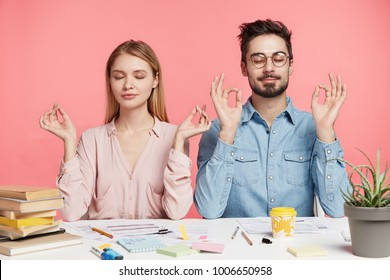Isolated shot of two female and male coworkers, meditate and keeps eyes shut, try to relax after exam preparation, cramm material from many books, sit at working desk against pink background