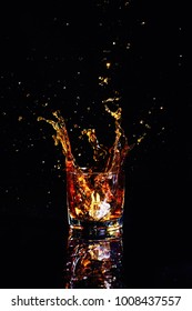 Isolated shot of whiskey with splash on black background, brandy in a glass