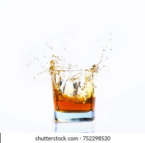 Isolated shot of whiskey with splash on white background, brandy in a glass