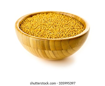 Isolated shot of yellow mustard seeds spice in traditional bowl against white background.
