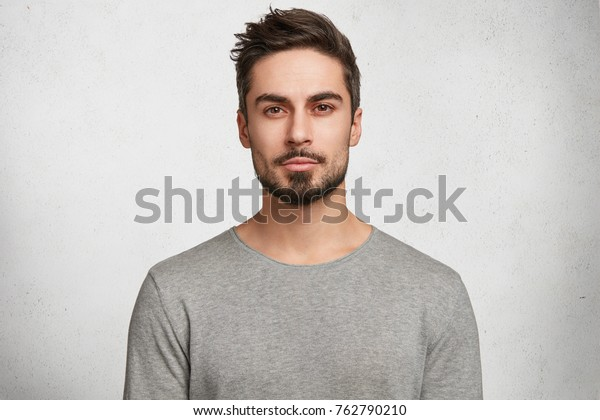 Isolated shot of young handsome male with beard, mustache and trendy hairdo, wears casual grey sweater, has serious expression as listens to interlocutor, poses in studio against white background