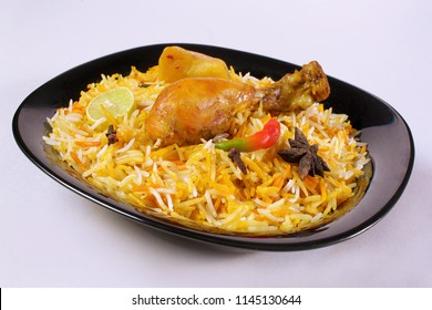 Isolated side shot of bombay biryani, Traditional spicy indian food, Iftar meal in black plate, Chicken rice Ramadan dinner on white background, Eid party.
