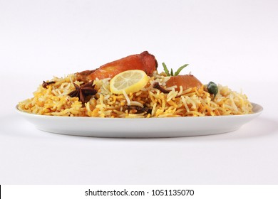 Isolated side view of chicken biryani with yogurt on white background, traditional spicy indian food. Pakistani fried rice. Ramadan dinner or iftar meal.