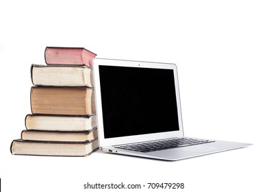 Isolated silver laptop with pile of old books