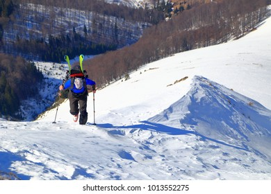 Isolated ski mountaineer walking on top of a mountain ridge