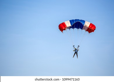 isolated skydiver control colorful parachute gliding after free fall jump with blue sky background  and copy space