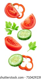 Isolated slices of vegetables. Falling cut cucumber, tomato and bell pepper (salad ingredients)  isolated on white background with clipping path