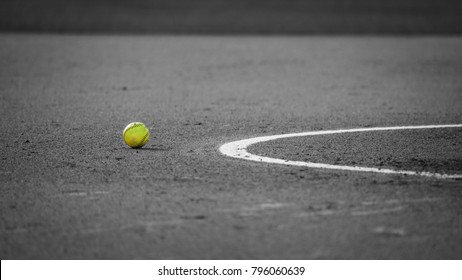 Isolated softball by itself on the field in the dirt