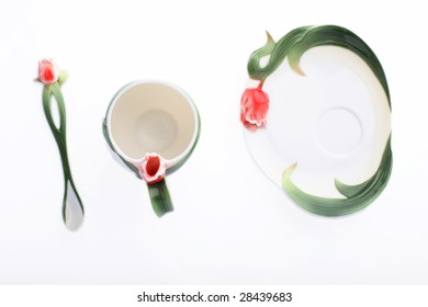 Isolated spoon, cup and sauser in a row on wihte background