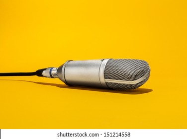 An isolated studio microphone hanging from above by it's cord facing down on a yellow background