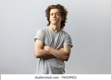 Isolated studio portrait of handsome self confident cool young American posing in studio with arms crossed and staring at camera with arrogant conceited look feeling proud of himself. Body language