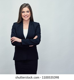 Isolated studio portrait of smiling business woman wearing black suit standing with crossed arms.