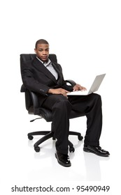 Isolated studio shot of an African American businessman sitting in a nice office chair while working on a laptop computer.