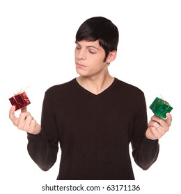 Isolated studio shot of a Caucasian man looking at presents, comparing a red one to a green.