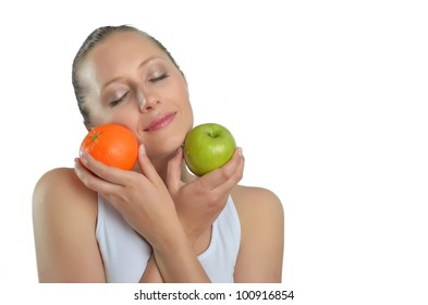 Isolated studio shot of a caucasian woman holding apples to oranges