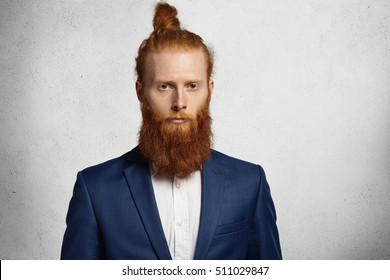 Isolated studio shot of young handsome redhead hipster man wearing trendy jacket looking serious and pensive at camera. Fashionable Caucasian businessman with stylish hair knot standing in office