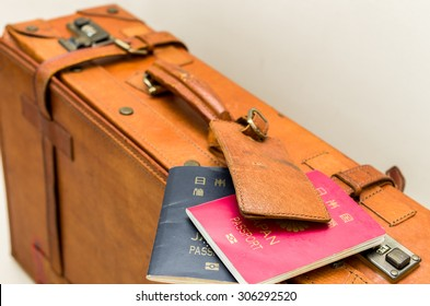 Isolated suitcase with Japanese passports on a white background