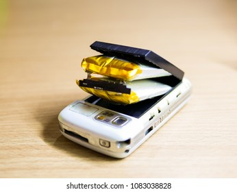 Isolated swollen battery with cell phone on desk.