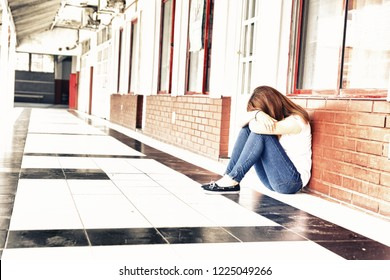 Isolated teenager girl seated desperate in the school hallway. Bullying concept.