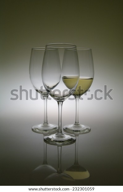 Isolated three white wine glasses, one filled.