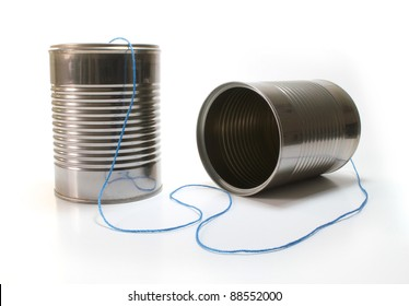 Isolated tin can telephone with blue thread.