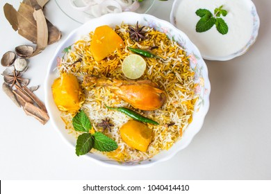 Isolated Top view of chicken biryani with yogurt on white background, traditional spicy indian food. Pakistani fried rice. Ramadan dinner or iftar meal.