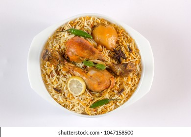 Isolated Top view of chicken biryani on white background, traditional spicy indian food. Pakistani fried rice. Ramadan dinner or iftar meal.