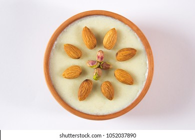 Isolated top view of kheer with almond topping, Beautiful dessert bowl on white background, Eid dinner meal.
