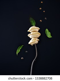 Isolated traditional russian pelmeni, ravioli, dumplings with meat and flying spice and bay leaves on black background. Design and food styling idea for sale. Menu or cook book concept