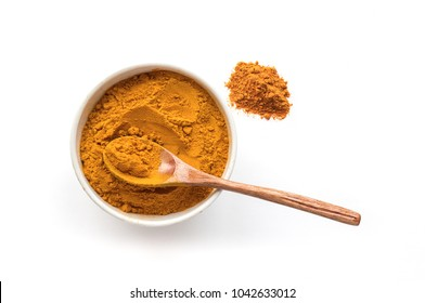 Isolated turmeric powder and wooden spoon. White background. Traditional indian spice. Top view.