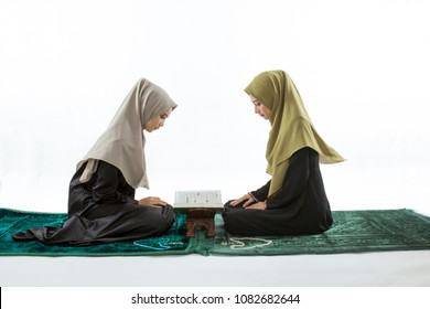 isolated two friends are recited al-Quran on a prayer mat in white background