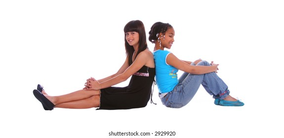 isolated two young girls sitting on the floor and leaning back to each other