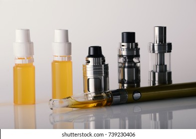 isolated vape tanks and e liquid for electronic cigarette or e cig over a white background. vaping rdta and e juice for vaping devices.