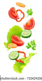 Isolated vegetables mix. Pieces of fresh tomato, cucumber, carrot, bell pepper and lettuce leaves (salad ingredients) in the air isolated on white background with clipping path