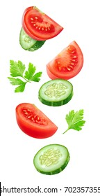 Isolated vegetables. Mixed slices of cucumber and tomato in the air isolated on white with clipping path