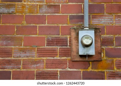 Isolated view of electrial meter mounted on weathered brick wall with open copy space to the left