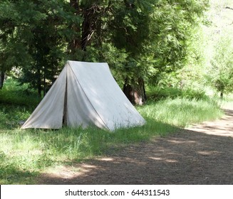 Isolated vintage canvas tent on dirt road.