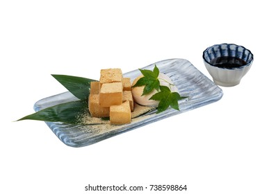 Isolated Warabimochi is a jelly-like confection made from bracken starch and covered or dipped in kinako (sweet toasted soybean flour) served with vanilla ice cream and maple syrup in glass plate.