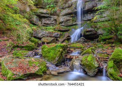 Isolated waterfall with stones covered with green moss.