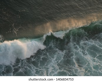 isolated waves from above, high viewpoint crashing wave at sunset, Bali, Indonesia, aerial view waves sunlight