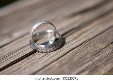 Isolated wedding rings on textured wood background