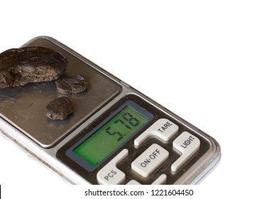 An isolated weighing scale with some hashish on it.