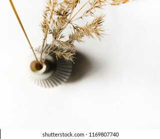Isolated white ceramic vase with bulrushes in it. Dry flowers bouquet over white background. Mock up white ceramic floral decor herbarium for home working space top view.