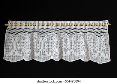 isolated white crocheted lace, a skein of yarn, a crochet pattern and the crochet hook on black background