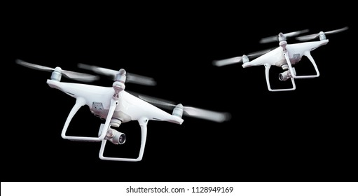 Isolated white drone with twirled propellers on black background