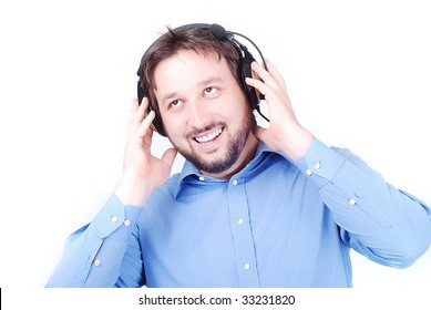 Isolated white man in blue shirt is listening to music on headphones